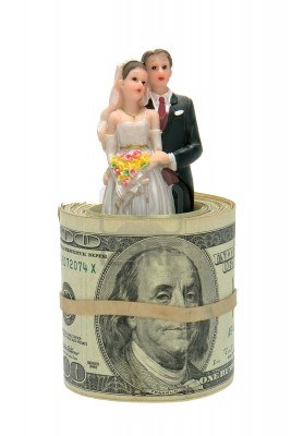 10318535-married-couple-bride-and-groom-figurine-inside-a-roll-of-us-dollar-banknote-bills-isolated-on-white