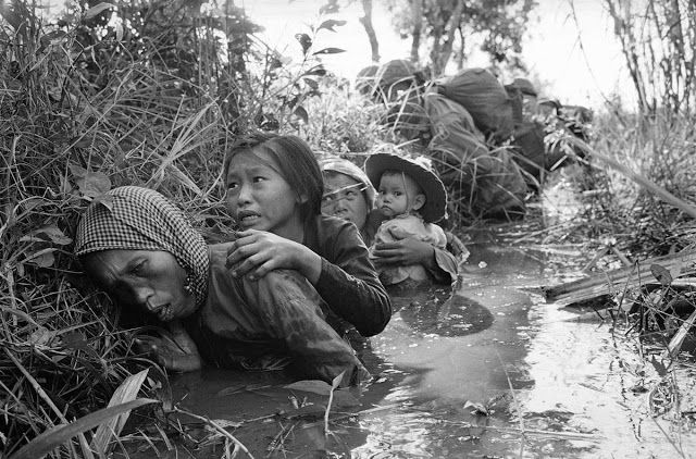 Vietnam War in Picture: Women and children crouch in a muddy canal as they take cover from intense Viet Cong fire at Bao Trai, about 20 miles west of Saigon on Jan. 1, 1966. http://tiny.cc/14stex